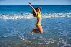 Bikini girl jumping in Caribbean sunset beach. Bikini teen girl jumping happyt in Caribbean sunset beach splashing shore Stock Photos