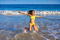 Bikini girl jumping in Caribbean sunset beach Stock Photo