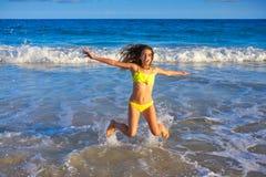 Bikini girl jumping in Caribbean sunset beach. Bikini teen girl jumping happyt in Caribbean sunset beach splashing shore Stock Photo