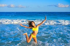 Bikini girl jumping in Caribbean sunset beach. Bikini teen girl jumping happyt in Caribbean sunset beach splashing shore stock image
