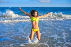 Bikini girl jumping in Caribbean sunset beach. Bikini teen girl jumping happyt in Caribbean sunset beach splashing shore Royalty Free Stock Photos