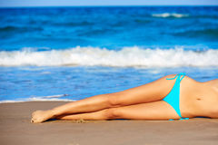 Bikini girl legs lying on beach sand in summer Royalty Free Stock Photography