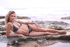 Bikini girl lying on a seaside rock Royalty Free Stock Images