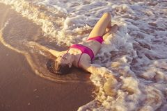 Bikini girl relaxed lying on the beach sand. Shore water of Mediterranean sea royalty free stock photo