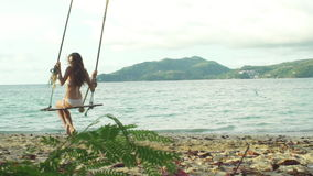 Bikini Girl Relaxing On Tropical Beach Paradise. Slow motion shot of a girl having fun swinging on a rope at tropical island beach stock video footage
