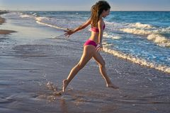 Bikini girl running to the beach shore water. Of Mediterranean sea royalty free stock images