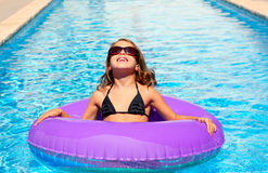 Bikini girl with sunglasses and inflatable pool ring Royalty Free Stock Images