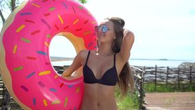 Bikini girl walking with sprinkled donut float at pool in sun day. Party, hotel, beach, holiday, vacation, travel. Smiling woman, summertime. Summer tenage stock video footage