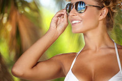 Bikini girl wearing sunglasses on palm tree Stock Image