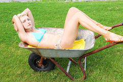 Bikini girl in a wheelbarrow. Royalty Free Stock Images