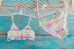 Bikini hanging from the fishing net on turqoise wooden backgroun Royalty Free Stock Photography