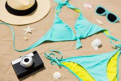 Bikini, hat, camera and sunglasses on beach sand stock image
