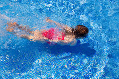 Bikini kid girl swimming on blue tiles pool Royalty Free Stock Image