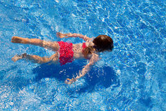 Bikini kid girl swimming on blue tiles pool Stock Photo