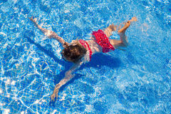 Bikini kid girl swimming on blue tiles pool Royalty Free Stock Photo