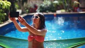 Bikini la mujer morena joven hermosa que lleva las gafas de sol y se sienta en selfie de las tomas de la hamaca con el teléfono p almacen de video