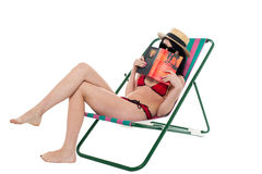 Bikini lady hiding her face with a book Stock Photos