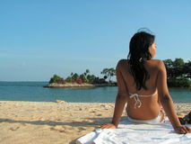 Bikini lady looking right. Sunbathing at a beach on the equator. The view is of a lagoon that connects to the sea Royalty Free Stock Photography