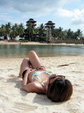 Bikini lady sunbathing. Suntanning lady lying down suntanning. Shot from behind her looking towards a tropical seaside with two towers. Area is Sentosa Island in Stock Photos