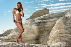 Bikini model. Attractive female bikini model on rocks royalty free stock photo