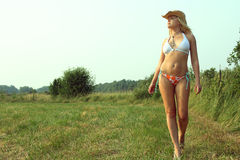 Bikini model. Concept image of a western style bikini model walking in a field Stock Photo