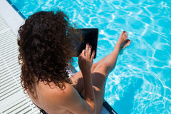 Bikini model holding touch pad with blank copy space screen for your advertising while sitting near hotel pool Stock Photo