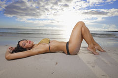 Bikini model laying on the sand Royalty Free Stock Photos
