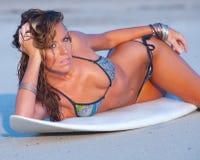 Bikini model. Lying on sandy beach next to surfboard stock photos