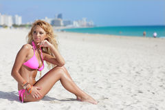 Bikini model sitting on the sand Royalty Free Stock Photography