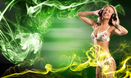 Bikini party. Attractive girl in white bikini and headphones on color background Royalty Free Stock Photos