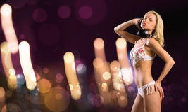 Bikini party. Attractive girl in white bikini and headphones on color background Stock Photography