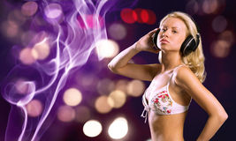 Bikini party. Attractive girl in white bikini and headphones on color background Stock Photos