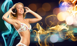 Bikini party. Attractive girl in white bikini and headphones on color background Royalty Free Stock Photography