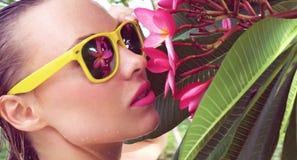 Bikini que lleva atractivo de la mujer joven con el pelo y la flor mojados del árbol en un día soleado Fotografía de archivo