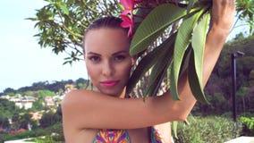 Bikini que lleva atractivo de la mujer joven con el pelo y la flor mojados del árbol en un día soleado Imagen de archivo