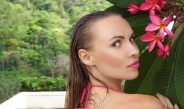 Bikini que lleva atractivo de la mujer joven con el pelo y la flor mojados del árbol en un día soleado Imagen de archivo libre de regalías