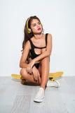 Bikini que lleva de la muchacha hermosa con los auriculares y el sentarse en el monopatín Imagen de archivo