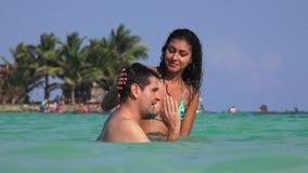 Bikini que lleva de la mujer con el hombre que flota en agua almacen de video