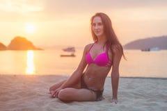 Bikini que lleva de la mujer morena joven atractiva del ajuste que se sienta en la playa del mar en la puesta del sol foto de archivo