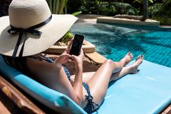 Bikini que lleva de la señora hermosa joven usando el teléfono móvil que sienta o Fotos de archivo libres de regalías