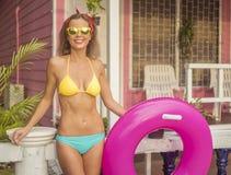 Bikini que lleva y gafas de sol de la mujer feliz bastante joven que presentan con el anillo inflable rosado en el fondo de la ca Foto de archivo
