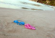 Bikini and shoes on tropical beach. Blue spotted bikini top with pink shoes on tropical beach Royalty Free Stock Images