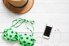 Bikini, sugrörhatt och smartphone på det vita trägolvet, bästa sikt Royaltyfria Foton