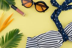 Bikini, Sunglasses and lip gloss. Decorate with bird of paradise flower and fern leaves on yellow background with copy space royalty free stock images