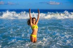 Bikini girl jumping in Caribbean sunset beach. Bikini teen girl jumping happyt in Caribbean sunset beach splashing shore Royalty Free Stock Image