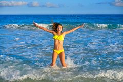 Bikini girl jumping in Caribbean sunset beach. Bikini teen girl jumping happyt in Caribbean sunset beach splashing shore Royalty Free Stock Photo
