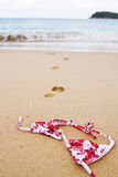 Bikini top lying on beach with footprints into surf Royalty Free Stock Photography