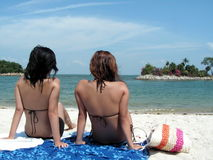 Bikini twosome at beach. Two ladies sunbathing themselves at a beach on the equator. Location is Sentosa Island in Singapore Stock Photography