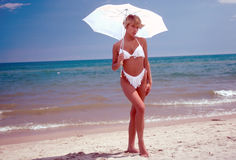 Bikini with umbrella. Standing semi-nude or semi nude swimsuited woman Michelle 21 years old plays with an umbrella over her shoulder and above her head while stock images