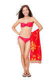 Bikini vacation holidays woman standing isolated. Holding red towel on white background in studio in full body length. Beautiful fresh multiethnic Asian Chinese Stock Photo